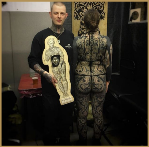 josh Fisher with an award next to one of his bodysuits