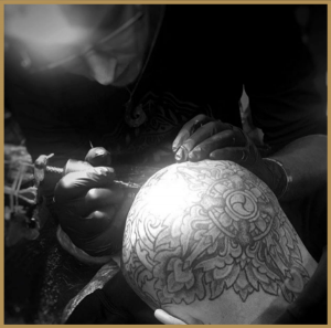 Josh Fisher tattooing a client's head